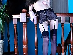 Slim leggy brunette in a black bustier with matching nylons on the stairs