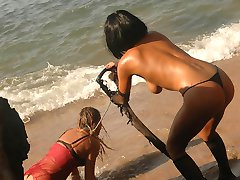 Topless domme in sexy fishnets punishing and strapon-fucking her sexy slave on the beach
