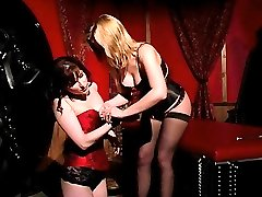 Sexy Lezdom scene with a blonde Domme with big natural boobs sitting on top of her submissive...