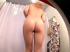 Blondie tries on a swimsuit in the voyeur fitting room