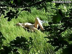 Spy on a nude girl sunbathing in a field
