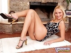 Smiling blonde in sexy dress stripping and spreading her pink pussy