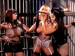 Cute blonde in bondage ball-gagged and cuffed in a prison cell by two kinky mistresses