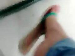 Candid teen dangling flat flip flops in the school