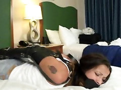 girl in arm binder and panel gag struggles on bed