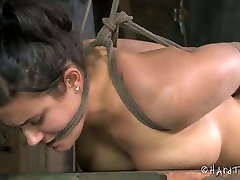 Suspended and tied up brunette moans of pain in bdsm room