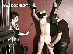 Blond hot slave gets tied to a wall and is spanked on her ass by mistress and master