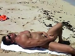 Muscular boy on the beach sperms his penis