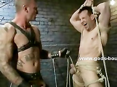 Gay sex slave gets bound and flogged by a dominating and tattooed