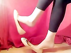 Sexy girl dangling with white flat shoe and stocking with black tight pant